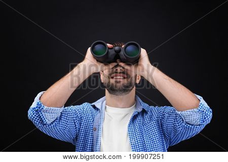 Handsome young man with binocular on dark background