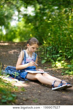 Girl Painter Draws In A Park Sitting On The Ground.