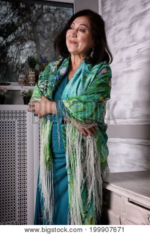 Mature Asian woman standing in green evening dress and with a shawl over their shoulders indoors.