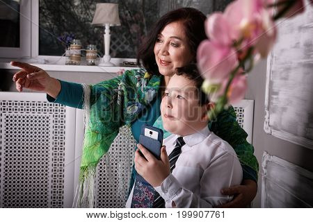 Grandmother showing something to grandson. asian family