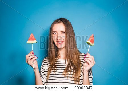 Summer, vacation, diet and vegans concept - Beautiful smiling young woman holding watermelon slice on stick.