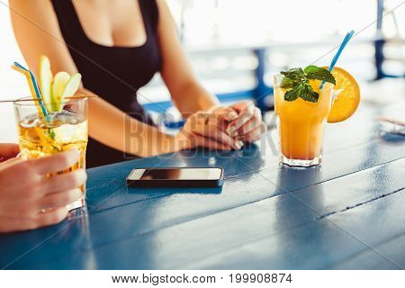 Cocktail in woman hand on the open terrace in bar during summer time. Summer bar