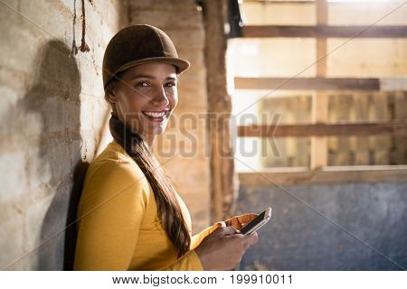 Portrait of smiling female jockey using mobile phone while standing by wall in stable