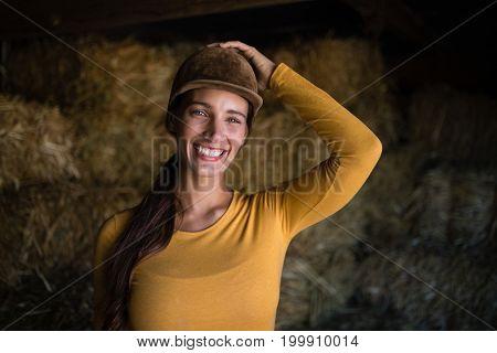 Portrait of happy female jockey standing against hay in stable