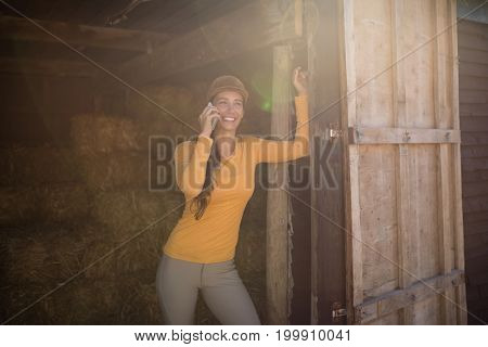 Smiling female jockey talking on mobile phone while standing in stable