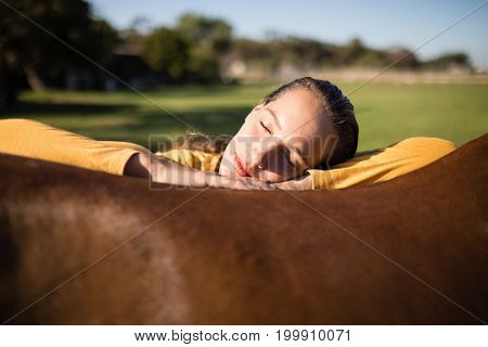 Female jockey with eyes closed relaxing on horse at barn