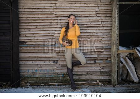 Female jockey talking on mobile phone while standing by stable
