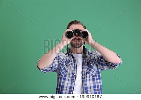 Handsome young man with binocular on color background