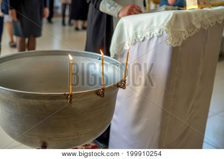Close up font with water for baptism with priest and rostrum in background in orthodox church