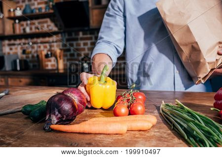 Cropped Shot Of Man Unpacking Vegetables At Kitchen