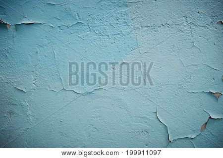 Grunge Background. Wall with the colored turquoise whitewash falling off fragment as a background texture cracked