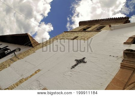 Colonial church with cross bells and clouds