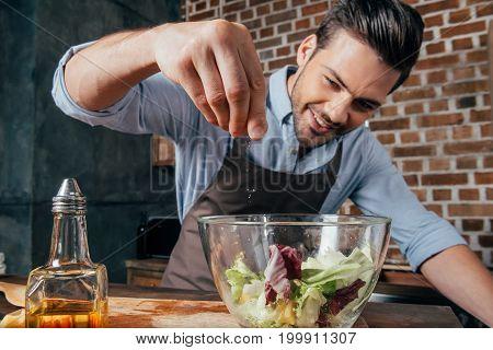 Man Adding Salt Into Fresh Salad