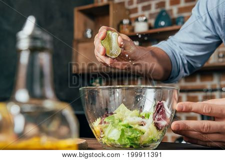 handsome young man squeezing lime into salad