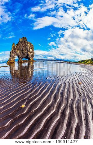 Rock Hvitserkur in the form of a huge mammoth on the sea beach. The north coast of Iceland. The concept of extreme northern tourism. Ocean tide at sunset