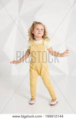 Beautiful little girl with blond hair, in yellow overalls on white background. Portrait of cute girl posing in studio.