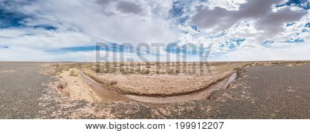 Dry river at center of safari at sunny day with cloudy sky on background