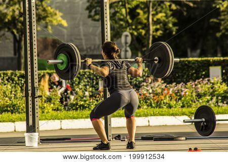 Woman doing sit-ups with a barbell on her shoulders on the street