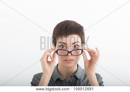 Strict woman in grey shirt and large glasses on white background.