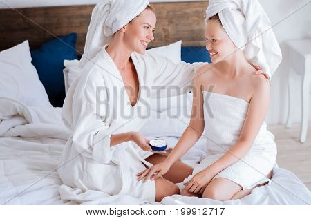 Friendly conversation. Amazing girl keeping smile on her face and sitting on the bed opposite her mom while having rest