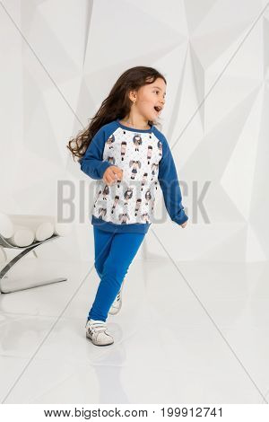 Adorable caucasian 5 year old girl running in white studio. The child is wearing a sweatshirt and blue pants