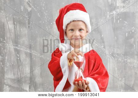 Cute little girl in Santa Claus suit with sand clock on grunge background. Christmas countdown concept