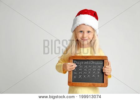 Cute little girl in Santa hat with chalkboard counting days until Christmas, on light background