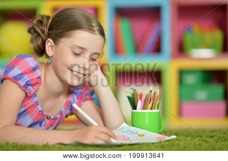 Cute schoolgirl lying on floor at home and doing homework