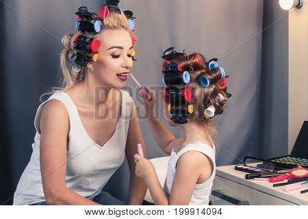 Pretty mother and her daughter having fun with lipstick while doing makeup and sitting at home. Young mother with her daughter in hair curlers, funny family