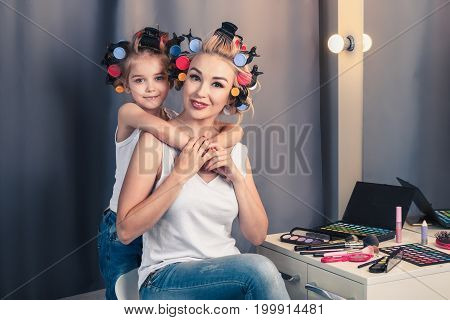 Beautiful young mother and her daughter with hair curlers are spending time together at home. Mom and daughter embrace