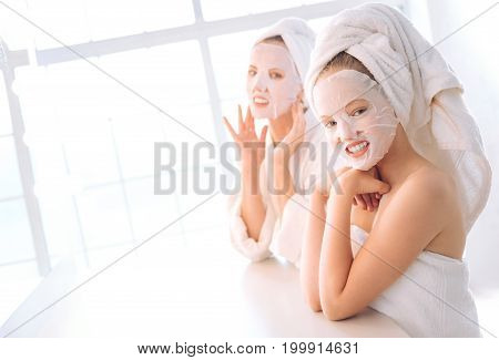 Wet your face. Charming girls standing in semi position and leaning on table while looking straight at camera
