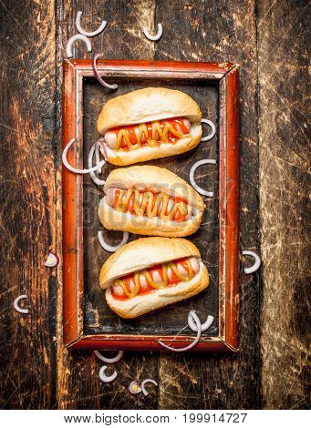 Hot Dogs With Mustard And Tomato Sauce On The Board.