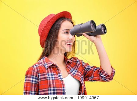 Beautiful young woman with binocular on color background