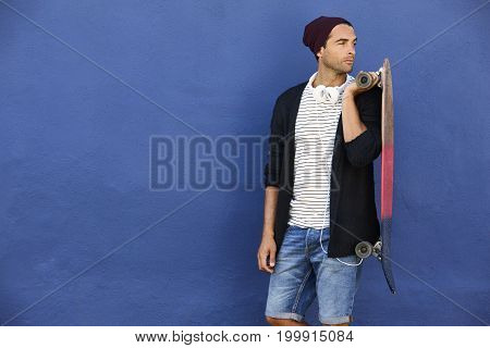 Dude holding skateboard and looking away against blue wall
