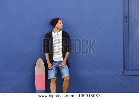 Skateboarder dude leaning on blue wall looking away
