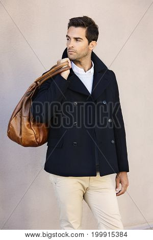 Smart dude in jacket carrying leather bag