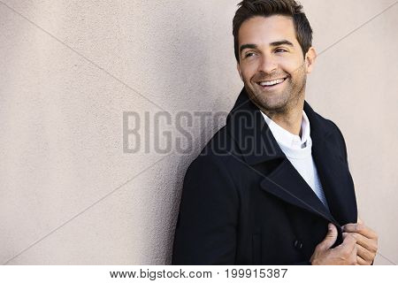Happy dude in jacket against wall smiling
