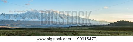 panoramic view of plain at root of mountains at sunny day
