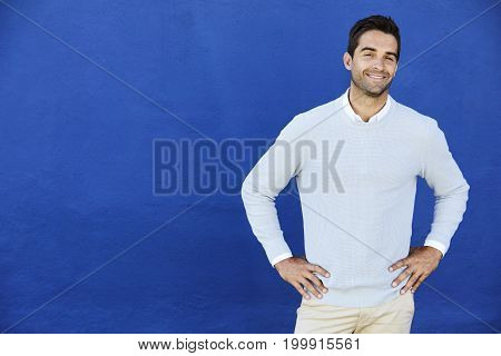 Blue sweater dude smiling against blue wall portrait