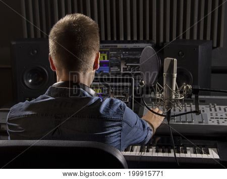 Musician working and producing music in his modern recording studio