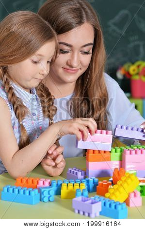 Mother and daughter playing with colorful plastic blocks with school blackboard on background