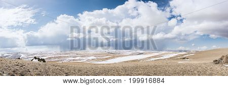 panoramic view of snow-capped mongolian prairie with cloudy sky on background