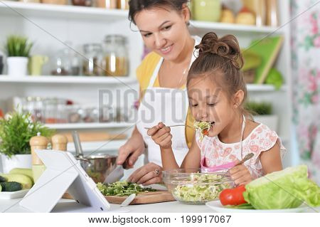 Mother and daughter cooking together with tablet on table