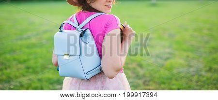Young female with blue backpack and hat enjoying the countryside view.