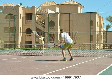 Husband and wife playing tennis at court
