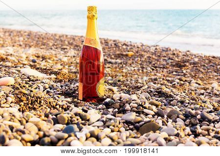 A Bottle Of Champagne, Beach And Sea.