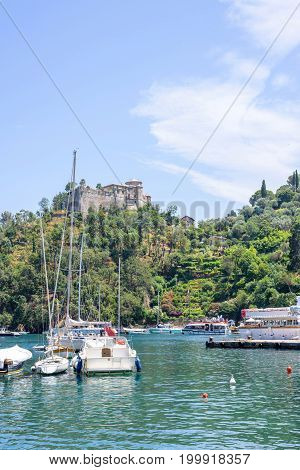 Daylight view to beauties of Portofino, Italy. Ships on water with people resting in them.