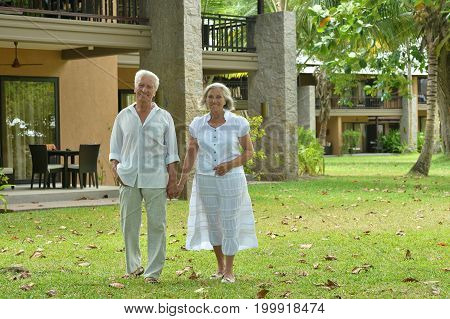 Senior couple holding hands  near  hotel resort