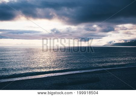 Sunset Over The Ocean On A Cloudy Day.