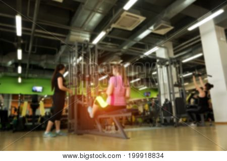 Gym background. Blurred picture of females exercising in modern fitness center.